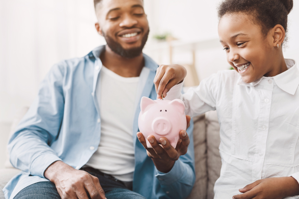 Man and child adding money to piggy bank